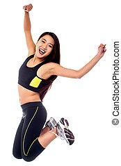 Girl in sportswear jumping with joy - Beautiful girl in...