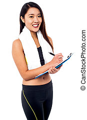 Female dietitian preparing diet chart - Young slim gym...