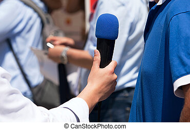 press interview - Journalist hand holding a microphone...