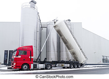 tanker truck refilling some large silos for food industry