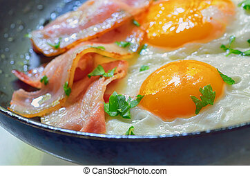 fried egg with bacon in a frying pan shoot in studio