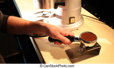 Barista compresses ground coffee