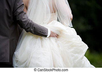 bride and groom - holding the dress