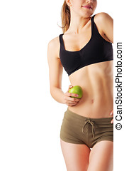 Sporty woman in fitness dress holding green apple isolated on white