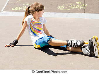 Teenager in rollerblades relaxing in the sun sitting on the...