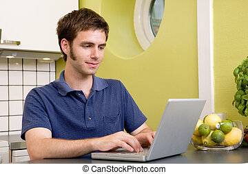 Online in the Kitchen - A young male using a laptop computer...