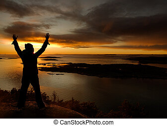 Ocean Celebration - A person standing by the ocean raising...