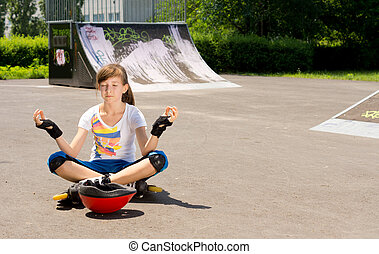 Girl in rollerblades sitting meditating - Pretty young...