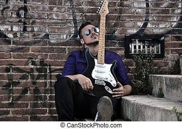 musician posing with his guitar in a wall of graffiti