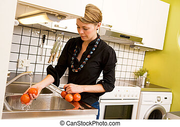 Female Washing Tomatoes - A woman is washing tomatoes in the...