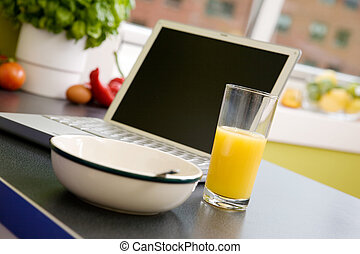 Online Breakfast - A computer in the kitchen with a bowl of...
