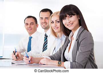 Business People Writing Meeting Notes In Office