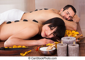 Beautiful Young Couple Enjoying Hot Stone Therapy In Spa...