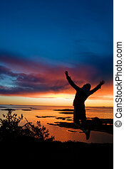 Ocean Cheer - A person jumping by the ocean raising their...