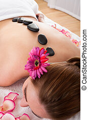 Happy woman getting hot stone therapy - Beautiful young...
