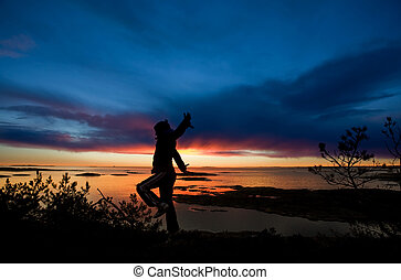 Ocean Cheer - A person running by the ocean raising their...
