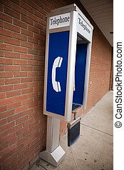 Pay Phone - A pay phone against the side of a brick building