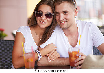 Happy time - Young guy and his girlfriend sitting in cafe on...