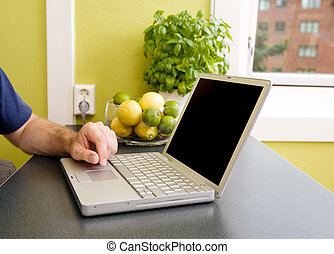 Kitchen Computer - A computer in the kitchen with a male...