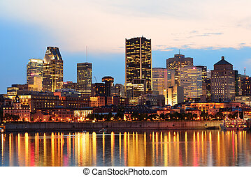 Montreal over river at sunset with city lights and urban...