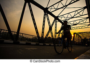 Man ride bicycle silhouette on bridge