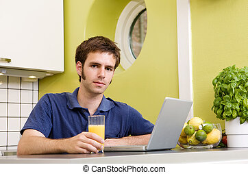 Kitchen Computer - A young male using a laptop computer in...