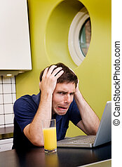 Worried Computer User - A worried computer user sits in his...