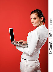 Female with Computer on Red - A young woman typing on a...