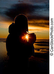 Ocean Silhouette - A person standing by the Ocean drink a...