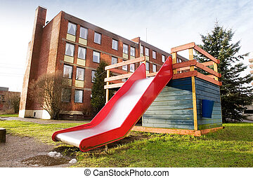 Playground Slide - A playground slide and jungle gym near an...
