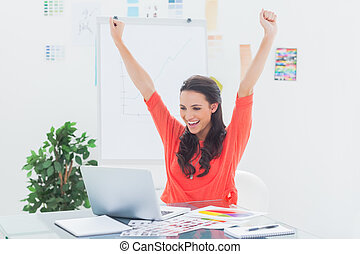 Excited woman raising her arms while working on her laptop...