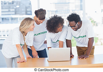 Smiling volunteers working together on a laptop in their...