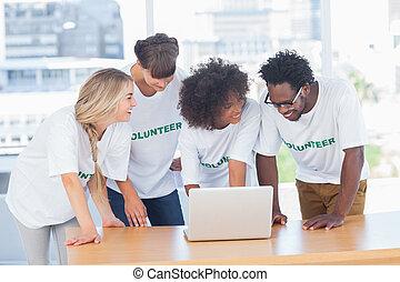 sorrindo, voluntários, trabalhando, junto, laptop