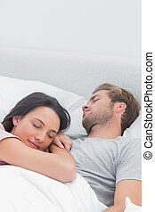 Pretty woman sleeping on her husbands chest in bed