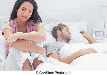 Stressed woman in her bed sat next to her sleeping partner
