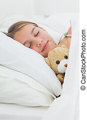 Cute girl sleeping with her teddy bear in her bed