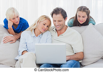 Children looking at parents using a laptop sitting on a...