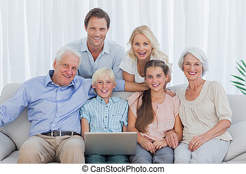 Extended family sitting on couch and using a laptop