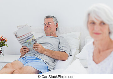 Mature man reading a newspaper in bed while his wife is...