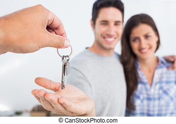 Man being given a house key - Man with his wife being given...