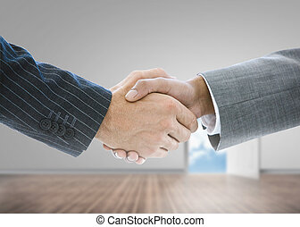 Close up of businessmen shaking hands in a grey room