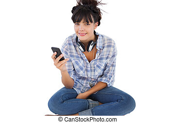 Happy young woman sitting on the floor with headphones holding her mobile phone on white background