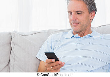 Man relaxing on his couch sending a text on smartphone at...
