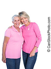 Mature women wearing pink tops and breast cancer ribbons on...