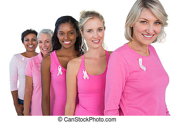 Group of diverse women wearing pink tops and ribbons for...