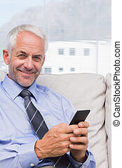 Smiling businessman using smartphone