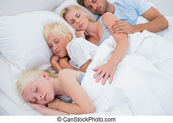 Couple sleeping with their cute children