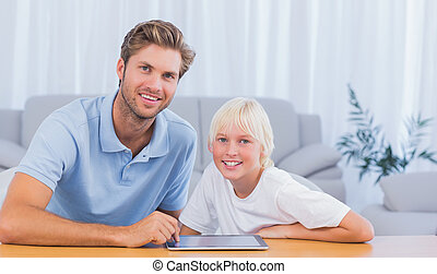 Father and his son using tablet in living room