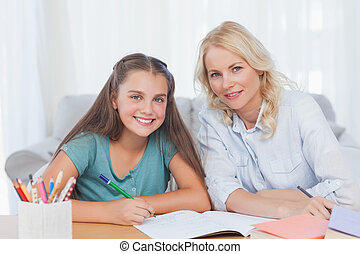 Woman helping her daughter doing her homework in living room