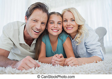 Portrait of a girl and her parents lying on a carpet